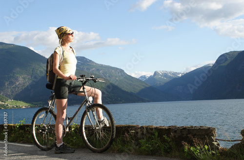 Photo Stands Cycling sporty woman on a bike trip in the mountains