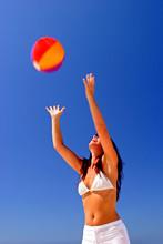 Girl Catching Beach Ball On Su...