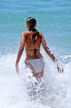 Young, Fit, Tanned Woman Walking Through A Wave Out To Sea.