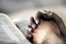 Praying Hands Over A Holy Bible