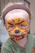 Young Boy Or Toddler Covered In Tiger Face Paint
