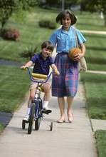 Mother Helps Son Learn To Ride...