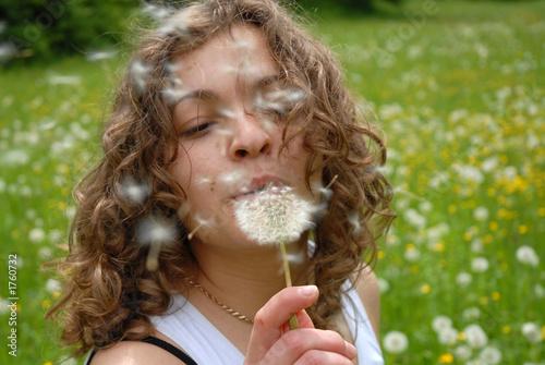 Fotografia  girl is blowing on dandelion