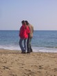 lovers on deserted beach by sea
