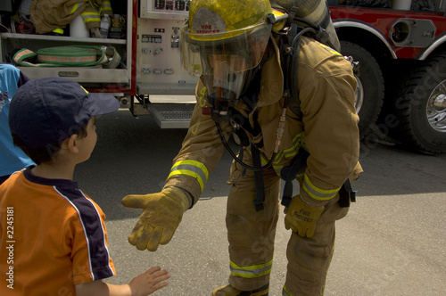 firefighter in uniform with a child Wallpaper Mural