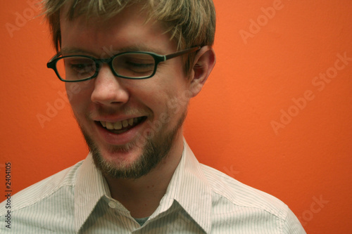 young man with glasses smiling, orange backdrop Fototapet