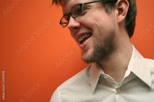 young man with glasses laughing, orange backdrop Tablou Canvas