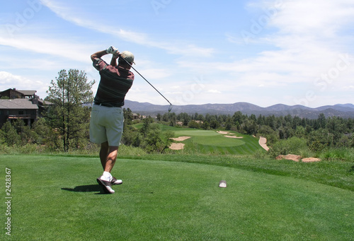 Photo golfer hitting golf ball off tee box on beautiful
