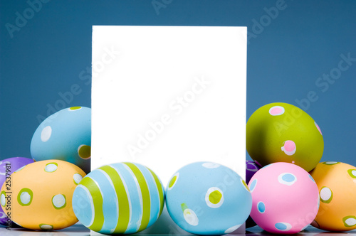 Photo  brightly colored easter eggs surrounding white, blank notecard