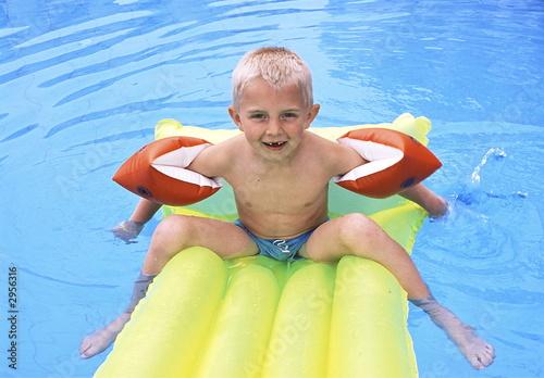 Fotografie, Obraz  8-year old boy on air mattress in a swimmingpool