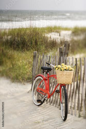 In de dag Fiets Bike leaning against fence at beach.