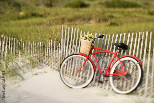 Tuinposter Fiets Bike leaning against fence at beach.