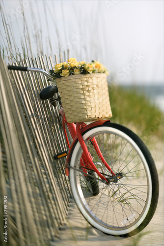 Deurstickers Fiets Bike leaning against fence at beach.