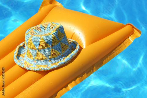 Fotografie, Obraz hat on orange airbed, floating in swimming-pool