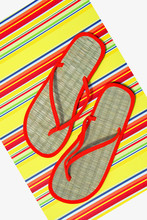 Straw Flip Flops On Colorful Mat