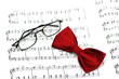 Bow tie and reading glasses on note paper