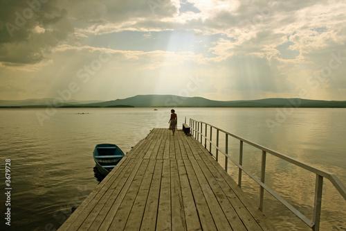Fototapeta the girl  silhouette over the lake background obraz