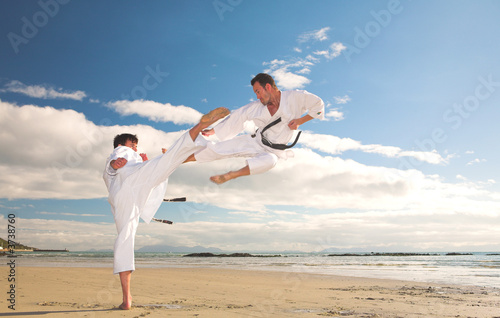 Young adult men practicing Karate on the beach Wallpaper Mural