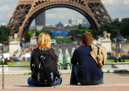 Foto  Young tourist couple sitting in front of Eiffel tower