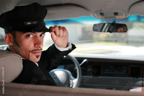 Fotografie, Obraz  Handsome male chauffeur sitting in a car saluting a viewer