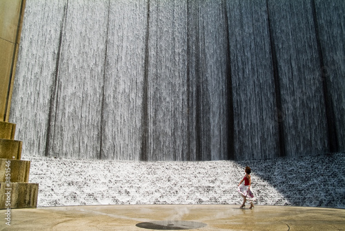 Photo A woman playing in the moist breeze of a waterfall