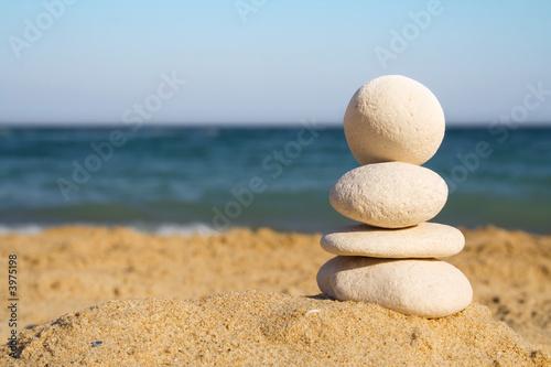 Photo sur Plexiglas Zen pierres a sable Stacked white pebbles on the beach
