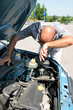 Businessman opening the trunk and checking the engine of a car