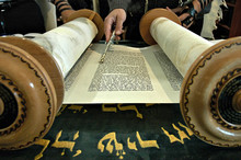 Torah  In A Synagogue With A Hand Holding A Silver Pointer