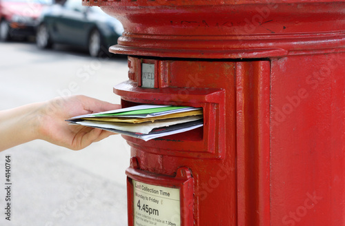 Photo posting many letters to red british postbox on street