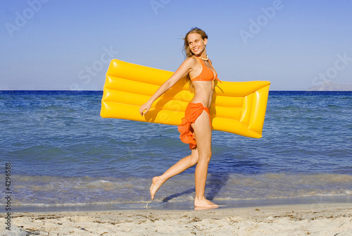 happy smiling woman strolling on seashore with lilo,airbed Wallpaper Mural