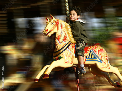 Fototapety, obrazy: Young boy thrilled on the carousel ride,