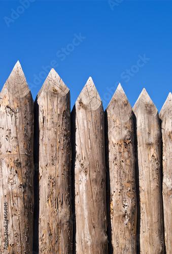Obraz na plátně High wall of old wooden sharpened logs over blue sky