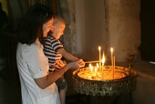 Mom And Kid Lighting Candles In A Church