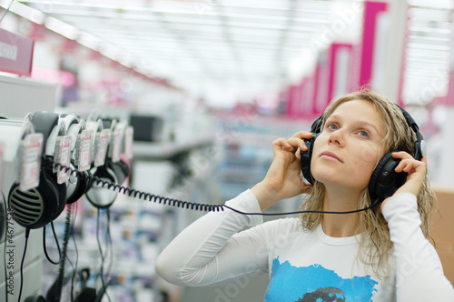 Foto auf Gartenposter Musikladen girl listening music with headphones in store