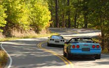 Two Sports Cars Driving On A Winding Road