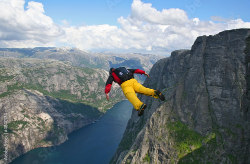 Fotografie, Obraz  base-jumper falling from cliff down to the fjord