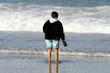 femme forte sur la plage, les pieds dans l'eau