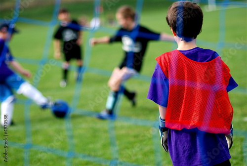 Photo  Young Goalie watching Kids Kick the Soccer Ball in front of Net