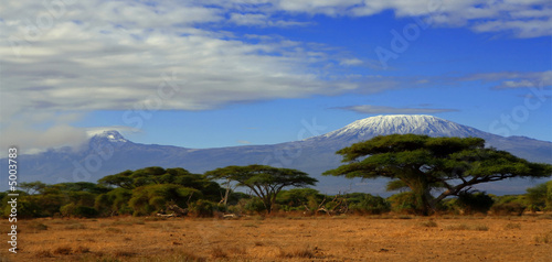 Staande foto Afrika Kilimanjaro Tanzania snow capped under cloudy blue skies captured whist on safari in Africa Kenya.