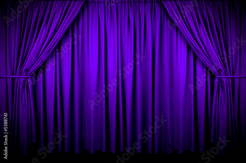 Large purple curtain with spot light and fading into dark.