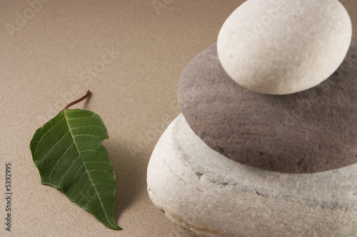 Photo sur Plexiglas Zen pierres a sable 3 galets en équilibre et une feuille verte