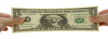 Hands Stretching A US Dollar N...