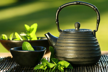 Fototapeta Herbata Black iron asian teapot with sprigs of mint for tea