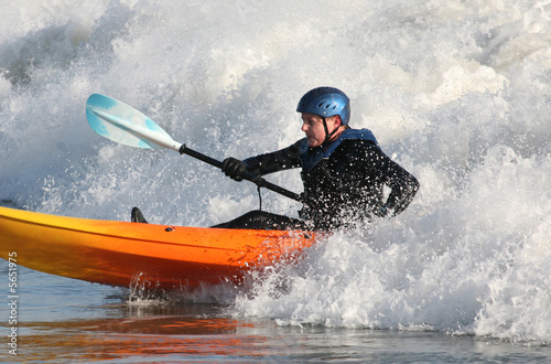 Valokuva  Kayak surfer paddling in rough seas