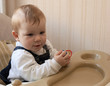 Adorable baby sits at a table