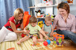 two mothers play with children in playroom