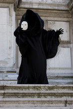 Black Figure On The Steps Holds White Face Mask. Masquerade