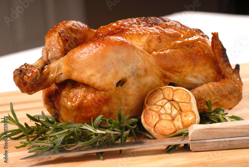 Fotografie, Obraz  Whole roasted chicken with garlic, rosemary and carving knife