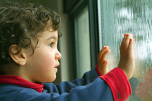 Little Boy Watching The Rain T...