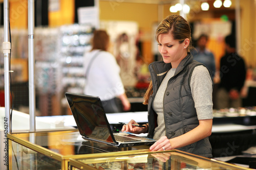 Fotografie, Obraz  Young businesswoman using laptop computer at trade show.